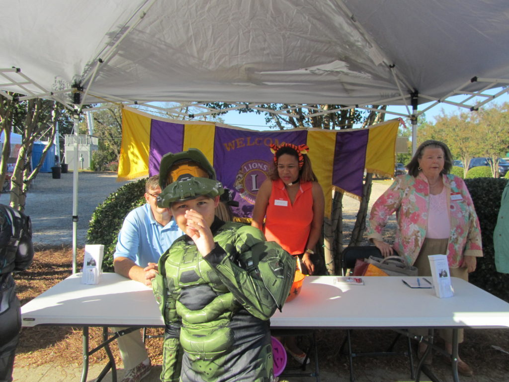 Picture of 1 child in costume turtle standing at Lions Club tent.